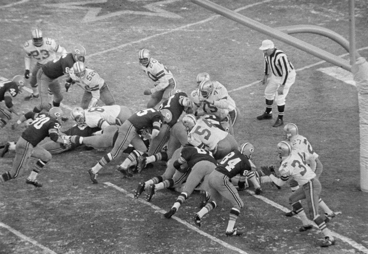 With seconds remaining, quarterback Bart Starr (15), Green Bay Packers, bulls his way behind the Packers' play leader - the center - and key blocker Jerry Kramer (64), who is delivering key block to Dallas' tackle Jethro Pugh (75), Dec. 31, 1967. Starr gave Green Bay a 21-17 NFL victory for its third year in a row. (AP Photo) ORG XMIT: APHS437868